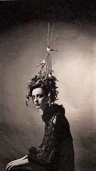 Sephia photograph of woman sitting, looking sadly at camera with a stick teepee and birds resting on her head.